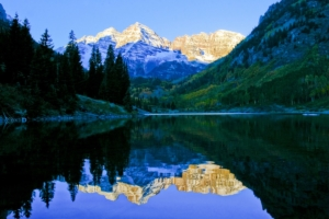 The Maroon Bells are reflected off a mountain lake