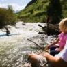 A family watches a kayaker navigate Gore Creek near Vail.